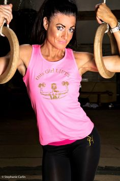 Model wears 'This Girl Lifts' racer back vest in pink with pink and black S.H embroidered exercise leggings.