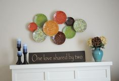 Create this cool focal point above the fireplace. You can simply use colorful plates and dishes assembled on the wall with different color combinations. Below the plates you can place a lovely quote written on the cardboard between the flower pots or vases. These simple elements can greatly enhance the look of your living room.