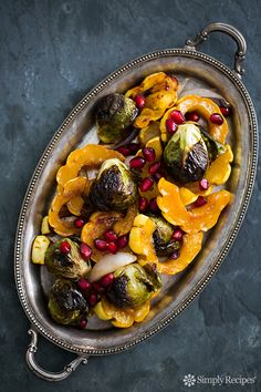 Maple syrup roasted delicata squash and brussels sprouts, with shallots and pomegranate seeds. So festive! Perfect side for Thanksgiving. On SimplyRecipes.com