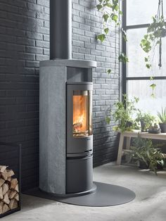 Contura 620T has a surround in heat retaining soapstone. The model has a cast iron door and a optional lower compartment cover.#soapstonestove #stovesinstone #logburner #brickwall #hangingflowerpot #interiordesingideas #contura600 #conturastyle