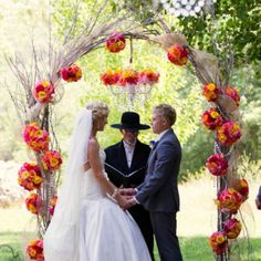 The ceremony featured an archway decorated with yellow and raspberry pink flowers. It was a beautiful backdrop as Sarah and Shawn read their custom vows to each other. The bride even made the chandelier hanging above them on the archway as well. Photo Credit: Stephanie Horwedel Photography