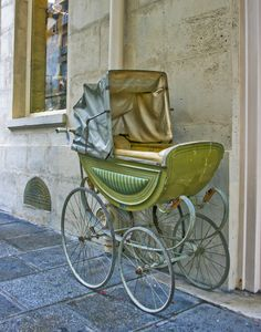 An antique baby buggy sits outside of a Paris shop.