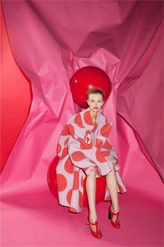 Kamila Filipcikova photographed by Charlie Engman. Red olka dots on a pink oversized robe coat, pink and red construction paper background, gorgeous glossy red T-strap pumps and a bold swipe of red lipstick.