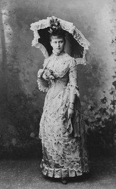 Elisabeth, Grã-duquesa Sergei da Rússia, de pé, em 08 de junho de 1887. Ela ergue a sombrinha aberta na sua mão direita, as luvas em sua mão esquerda. Pano de fundo de bosques.