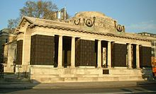 """The Tower Hill Memorial is a national war memorial on the south side of Trinity Square Gardens, just to the north of the Tower of London. It commemorates those from the Merchant Navy and fishing fleets who died during both world wars and have """"no grave but the sea"""".  The First World War memorial takes the form of a vaulted corridor, 21.5 metres long, 7 metres wide and 7 to 10 metres high. Inside are 12 bronze plaques engraved with 12,000 names."""