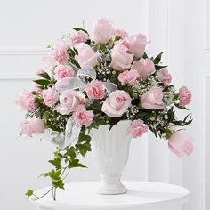 Turn your grief into a beautiful display of love and respect for the dearly departed. Deliver a gift of warmth and grace to the funeral or memorial, like this stunning combination of pink roses and carnations with delicate baby's breath, variegated ivy and vibrant greenery in a grand pedestal vase. This gorgeous arrangement expresses your wishes for peace and comfort during the saddest of occasions. Size is approximate.