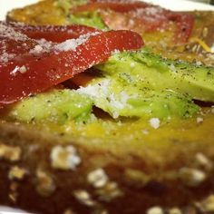 A simple, healthy breakfast--whole grain toast with melted cheese, avocado, tomato and grated parm!