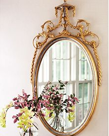 Adam style carved wood and wrought iron oval mirror with leaf drops and floral design