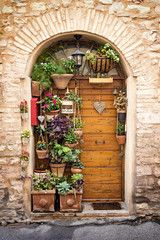 The beautiful wooden door decorated with lots of flowers and plants