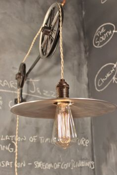 Perfect for pouring over blueprints or tinkering with prototypes. Built by hand with industrial grade components. Enter: the industrial pulley lamp. Both pulleys rotate freely, allowing the drape of the pendant lamp to be raised or lowered at will.
