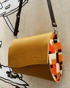 Modello ovale in pelle con laterali in legno decorati in tarsia.