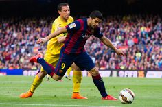 Luis Suarez of FC Barcelona competes for the ball with Roberto Lago of Getafe CF during the La Liga match between FC Barcelona and Getafe CF at Camp Nou on April 28, 2015 in Barcelona, Catalonia.