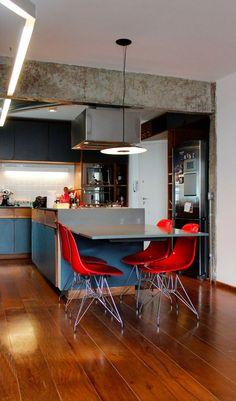 Reforma em apartamento na Chácara Klabin - A cozinha com piso de madeira integrada a sala de estar possui uma bancada central com tampo em marmoglass cinza que se estende transformando-se em uma pequena mesa de jantar suspensa. A viga de concreto aparente marca a antiga divisão dos ambientes. ______________________________ Chácara Klabin apartment renovation - Kitchen and dinning room #redchair #kitchen #dinningroom #concrete