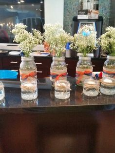 Mason jars big and small for rustic wedding shower.  Baby's breath in big jars. Lace burlap and orange and navy blue ribbon.  Floating candles in small jars with twine around the top.