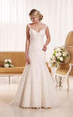 This stunning lace fit-and-flare bridal gown from Essense of Australia features fashionable tip-of-the-shoulder straps, and stunning scalloped lace detailing on its back and hem. The back zips up under matching fabric buttons. Fit-and-flare wedding dresses work wonders to add feminine curves to any body shape.