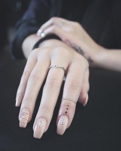 small dots, tattoo on the finger, cute finger tattoos, nude nail polish with rhinestones, black shirt Finger Tattoo Frauen, Finger Tattoo Herz, Crown Finger Tattoo, Lion Tattoo On Finger, Middle Finger Tattoos, Girl Finger Tattoos, Finger Tattoos For Couples, Finger Tattoo For Women, Red Heart Tattoos