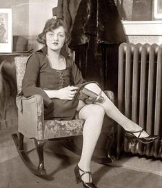 """'""""Safety first"""" is the motto of Miss Mary Jayne of Keith's circuit. Mary Jayne, seated in rocking chair with pistol strapped to her knee, claiming exemption from concealed weapon regulation by saying her thirty-two isn't a concealed weapon in these days of knee-length skirts.'"""
