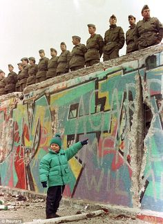 A young West German girl points to a large hole in the Berlin Wall,1989