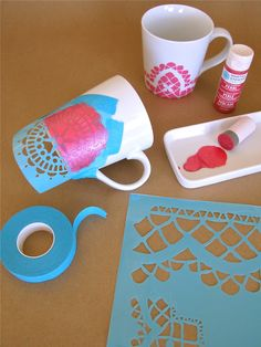 stencilling on the mugs...apply pearl paint over the taped-on stencil.