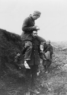 British prisoner carrying a German wounded on his back to the dressing station. German soldier appear to be writing some directions for his transport. - iwm