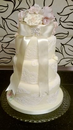 Thisi s a pale lemon wedding cake with white edible lace and hand painted sugar flowers.