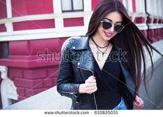 Outdoor lifestyle fashion portrait of young stylish hipster woman walking on street,wearing cute trendy outfit.Young woman with long dark hair  smiling to camera in city on city building background.
