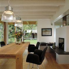 Eckiger Holztisch vor Panoramakamin mit bodentiefen Fenstern