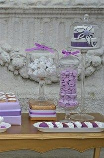 Glass displays showcase a variety of desserts, from lilac sweetheart candy to a miniature white and purple lemon cake.