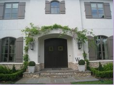 Could we borrow from this for our exterior? Shutters? Black door, boxwoods, vines