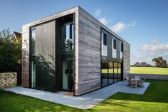 A slightly cantilevered home in England connects with nature.  In the countryside near Oxford, England, Adrian James Architects designed a house that achieves architectural distinction using prefabricated elements. Built out of flat-packed, insulated panels, the home cantilevers over a concrete wall, creating a captivating entrance. Sizeable windows offer a connection with the green expanses outdoors. On the inside, meanwhile, the home allows for open-plan living and, thanks to neat touches…