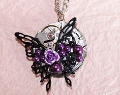 Steampunk Necklace: This Steampunk timepiece puts on spotlight a black ornate butterfly accented with a purple rose & silver vintage CROTON Swiss watch movement with genuine ruby jewels. Croton is a celebrities' watch brand that really doesn't need an introduction, as it is often wore by Hollywood stars like Josh Groban, Quincy Jones, Taylor Shift, Miley Cyrus, Natalie Cole, and Joe Mantegna, just to name a few.     This gorgeous Steampunk timepiece is further adorned with purple ...