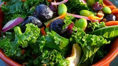 This kale salad recipe delivers a big bowl of vegetables, fruits, nuts, and seeds for a filling potluck favorite.