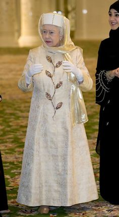 November 24, 2010 The Queen visits Sheikh Zayed Grand Mosque, Dhabi. The Queen wore a gold brocade coat embroidered with Swarovski crystals over her matching dress, both designed by her dresser, Angela Kelly. She tied a gold lame shawl over her pillbox hat to cover her hair.