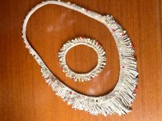 Ketting en armband, gemaakt van witte katoen met glaskralen. Geverfd met walnotenbast en uienschillen