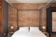 Sleep tight in our Walden apartment. Soft bed against a brick accent wall