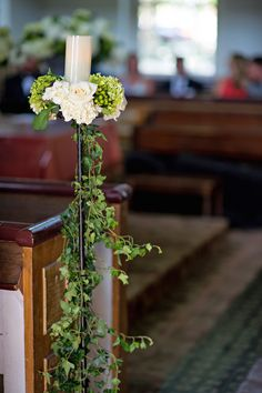 Metal stands draped in ivy vines and topped with a pillar candles nestled among vanilla and green blooms decorated the ends of the church pews. #ceremonydecor #candlestand Photography: Kristen Weaver Photography. Read More: http://www.insideweddings.com/weddings/a-rustic-elegant-summer-wedding-in-the-pennsylvania-countryside/657/