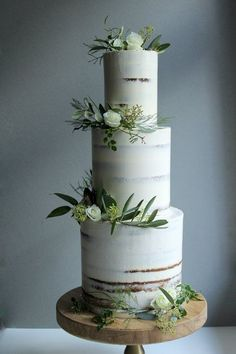 Minimal semi-naked tall three tier cake. Simple white and green wedding cake.