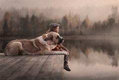 Elena Shumilova's magical, wintry photography: Boy and dog on lake dock