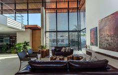 Decoração de casa, casa, arquitetura contemporânea e minimalista. Na sala sofá, almofadas, mesa de centro de madeira, poltrona estofada, obras de arte, quadros, plantas e luz natural.