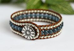 October Special Price, Reduced by $8.00!  This beaded leather cuff features 3 rows of glass beads and genuine leather. Metallic silver seed beads surround a center row of denim blue. Each bead is hand stitched between rows of distressed light brown leather. For a touch of country charm this bracelet fastens easily with a daisy button clasp. Fits up to a 6 1/2 wrist. Measures 7 1/2 and 3/4 wide. If you would like me to make this bracelet in another size for you, please leave your wrist size…