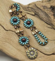 A charming bracelet in a floral design beaded with Czech glass beads. The floral motifs consist of pearl coat teal Super Duos surrounding a