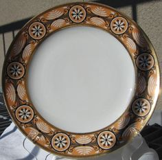 """James Madison Whitehouse 10"""" porcelain plate made by The Nast factory, circa 1806. Undecorated center, the orange-ground rim painted in black and thick white enamel with a neoclassical border of nine floral and foliate medallions alternating with fern and scroll devices between gilt bands."""