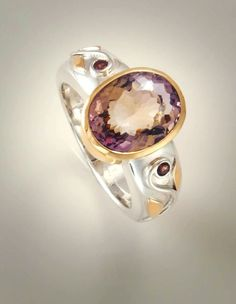Ring: Sterling silver band set with oval ametrine in 9ct gold with floral motif on shoulders and set with rhodolite garnets.