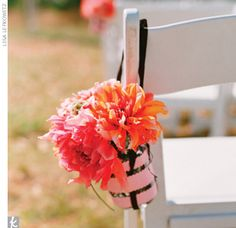 wrapped mason jars in paper and ribbon, then filled them with dahlias and hung them on the chairs lining the center aisle.