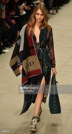 Model Cara Delevingne presents a creation from designer Burberry Prorsum during the 2014 Autumn / Winter London Fashion Week in London on February 17, 2014. AFP PHOTO / BEN STANSALL