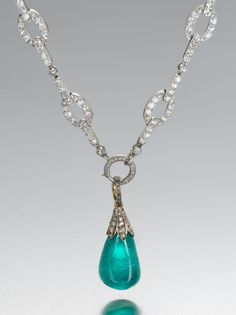 An early 20th century emerald and diamond sautoir, by Cartier, circa 1910. Designed as a series of old brilliant-cut diamond oval links with rose-cut diamond highlights to diamond bar and collet spacers, suspending an emerald pendant with rose-cut diamond cupola surmount
