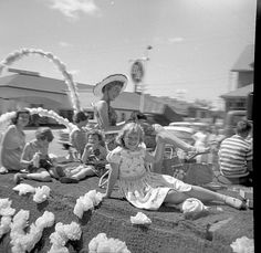 Image of a woman wearing a sun hat sitting in a lawn chair on a float - six children and picnic baskets surround her