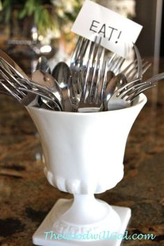 When hosting buffet-style dinners, The Goodwill Gal keeps flatware in a milk glass pedestal planter for easy access.