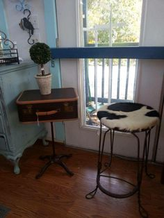 Vintage suitcase nightstand on an antique iron stand.