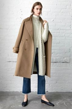 This cozy neutral look is a welcome sight among all the black monochrome looks we usually gravitate towards for fall and winter. We always love a good camel coat and this one goes perfectly with cream sweaters, raw-hem jeans and glove-style flats.
